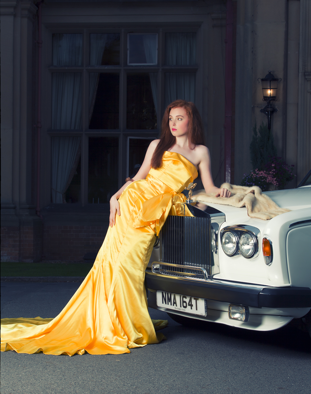 luxurious gold fall of the dress and the red of the models hair drape over a Rolls Royce