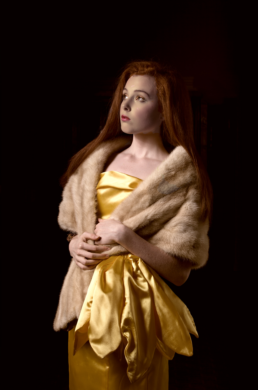 fur stole complements the luxurious gold fall of the dress and the red of the models hair